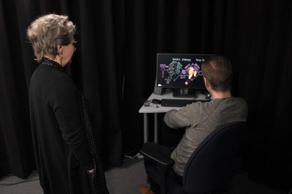 Kaksi ihmistä tietokoneen näytön ääressä Lightboard-videotilassa