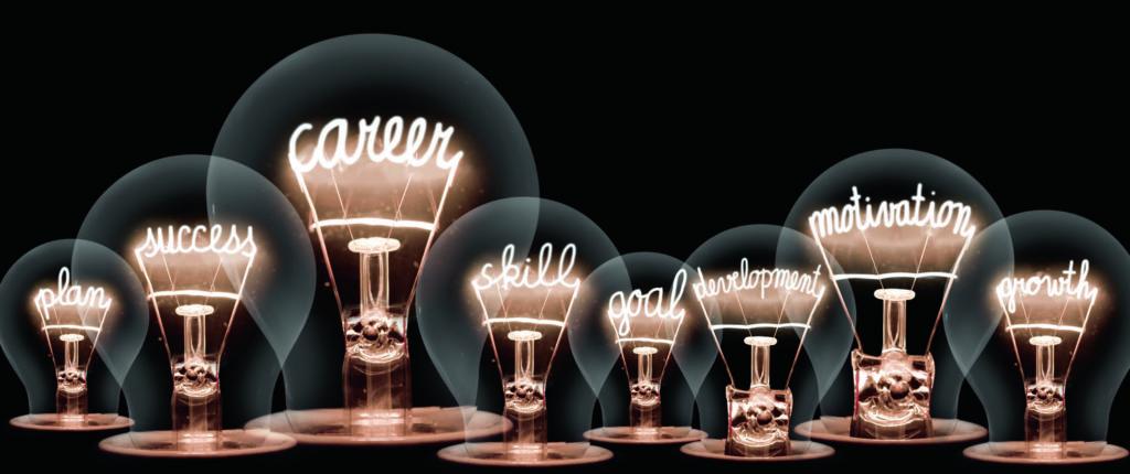 Hehkulamppuja, joissa englanniksi tekstit: plan, success, career, skill, goal, development, motivation, growth
