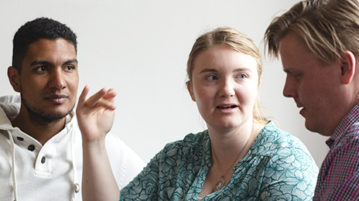 Kolme opiskelijaa keskustelemassa