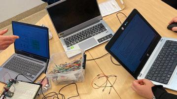 Kolme kannettavaa tietokonetta pöydällä