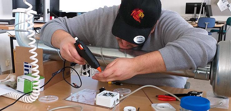 Mies yhdistämässä elektronisia osia toisiinsa