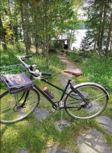 Pyörä edustalla, mökki ja järvi hiekkatien päässä taustalla