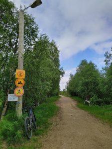 Pyörä nojaa katuvaloon leveän hiekkatien varrella, jossa ainoastaan pyöräily sallittu