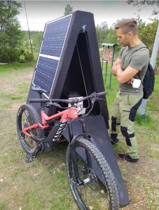 Kuva aurinkokennolatausmajasta, jonka vieressä maastopyörä ja ihminen.