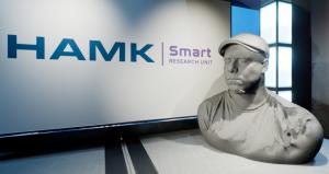 Topin 3D-skannattu pää ja HAMK Smart -tutkimusyksikön logo