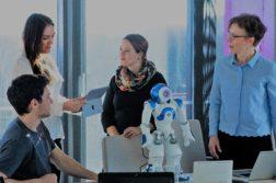 Neljä henkilöä tarkastelemassa NAO-robottia