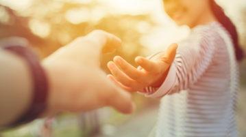 Tyttö hymyilee ja ojentaa kättään