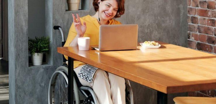 nainen pyörätuolissa tietokoneen äärellä