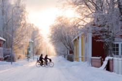 Kaksi pyöräilijää lumisessa Hämeenlinnassa