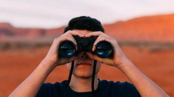 Poika kiikarit silmillä