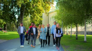 Hymyileviä ihmisiä kävelemässä Visamäessä