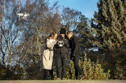 Kolme ihmistä tarkastelee dronea syksyisessä maisemassa.