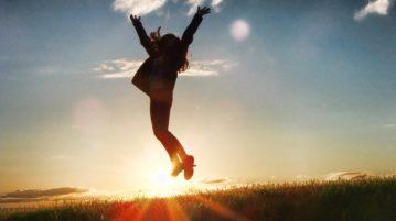 Ihminen hyppää ilmaan. Taustalla auringonpaiste