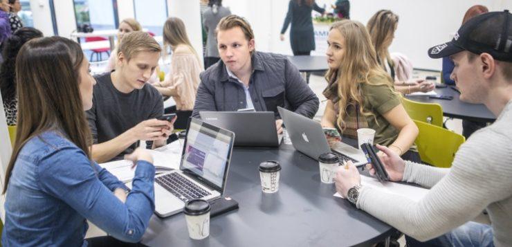 Opiskelijoita pöydän ympärillä