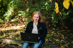 Kuvituskuva. Tyttö istuu puistossa läppäri sylissään.