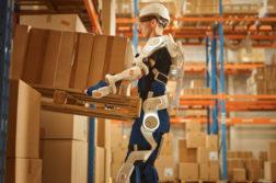 varastomies nostaa kuormaa pukeutuneena eksoskeletoniin