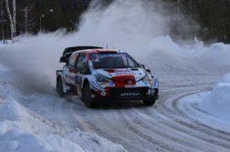 Punavalkoinen ralliauto ajaa lumisella tiellä