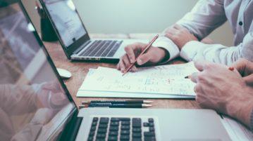 Kaksi tietokonetta pöydällä ja kahden henkilön kädet tekemässä muistiinpanoja kynällä paperiin.
