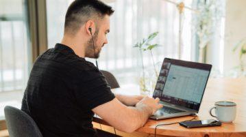 Mies on nappikuulokkeet korvissa ja istuu pöydän ääressä tietokoneella.