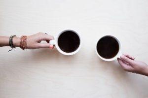 kaksi kahvikuppia, kaksi kättä