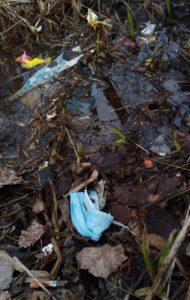 Vesistöön ajautunut kasvomaski, seuranaan tupakantumppi.